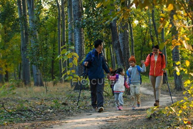 Feliz jovem asiático família com mochilas e trekking varas andando juntos na floresta — Fotografia de Stock