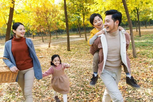 Pais jovens felizes com dois filhos adoráveis caminhando juntos no parque outono — Fotografia de Stock