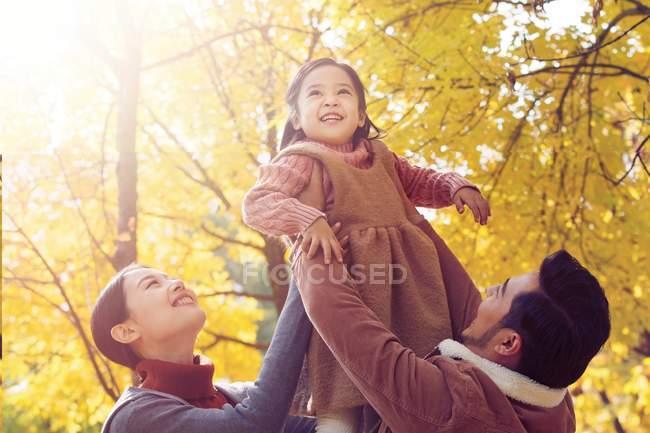 Щасливі азіатські батьки підйомом дочка в Осінній Парк — стокове фото