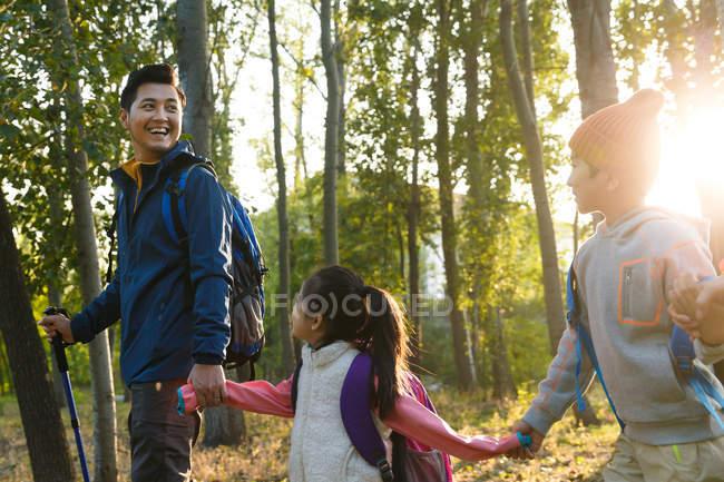 Padre felices cogidos de la mano y caminando con los niños en el Parque - foto de stock