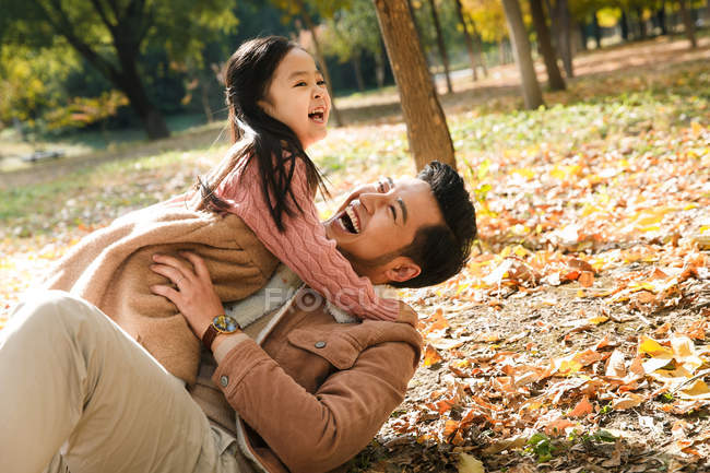 Feliz padre e hija que se divierten en el Parque otoño - foto de stock