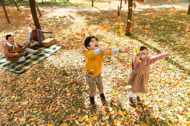 High angle view of happy kids playing with autumn leaves while parents resting on checkered plaid in park — Stock Photo