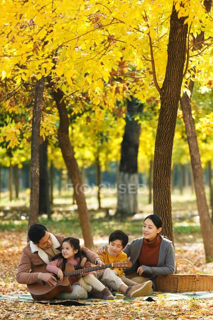 Feliz jovem asiático família sentado no xadrez e desfrutar de guitarra durante piquenique no parque — Fotografia de Stock