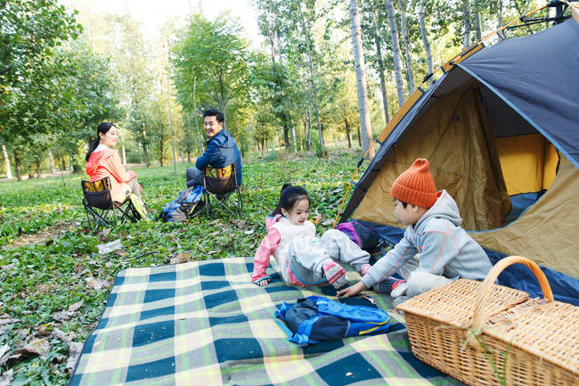 Adorable kids playing near tent and happy parents sitting on chairs in forest — Stock Photo