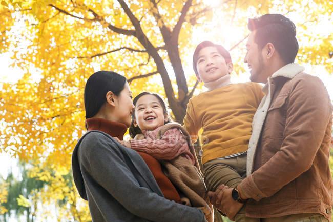 Tiefansicht glücklicher junger Eltern, die entzückende Kinder im herbstlichen Wald tragen — Stockfoto