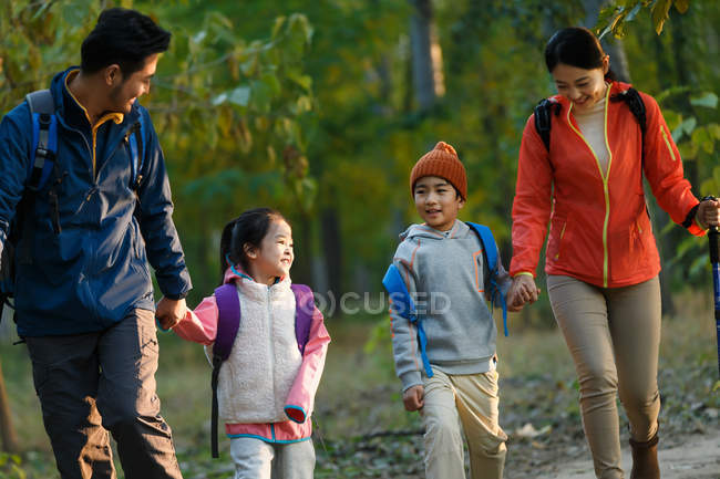 Happy young asian family with two kids hiking in forest — Stock Photo