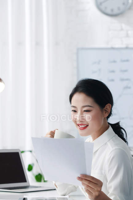 Attractive smiling asian businesswoman drinking coffee and reading documents in light office — Stock Photo