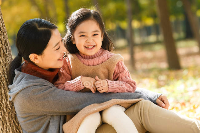 Happy asian mother and daughter sitting and hugging in autumn park — Stock Photo