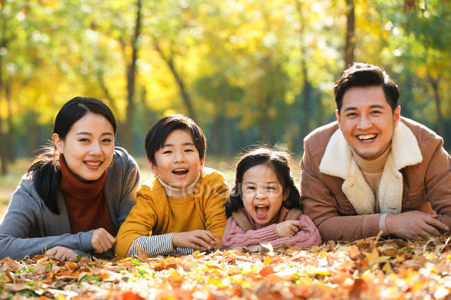 Happy young parents with two kids lying together and smiling at camera in autumn park — Stock Photo