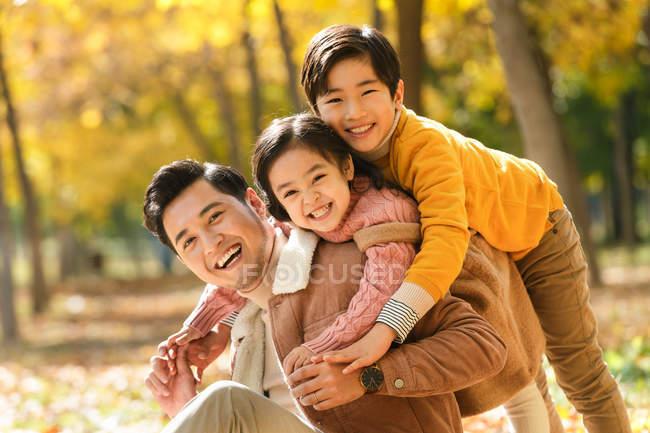 Счастливый отец с дети веселятся в Осенний парк — стоковое фото