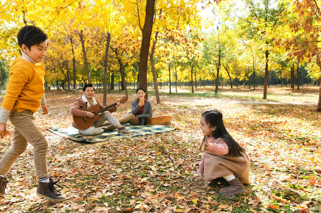 Adorable happy children playing with autumn leaves and parents enjoying guitar during picnic in forest — Stock Photo
