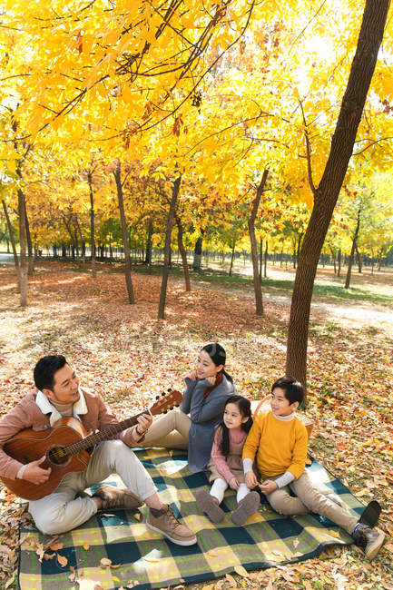 High angle view of happy family spending time with guitar in autumn park — Stock Photo