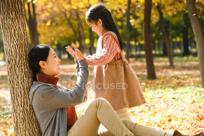 Side view of happy asian mother and daughter playing together in autumn park — Stock Photo