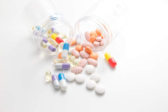 Scattered pills from jars on white surface — Stock Photo