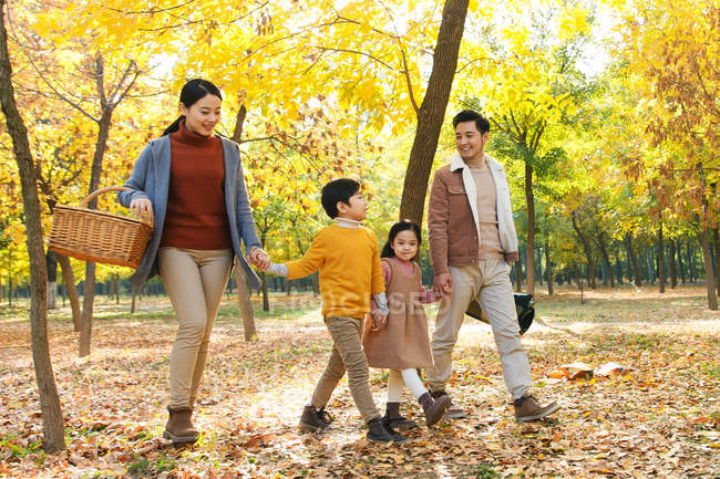 Happy young asian family with picnic basket walking together in autumn park — Stock Photo