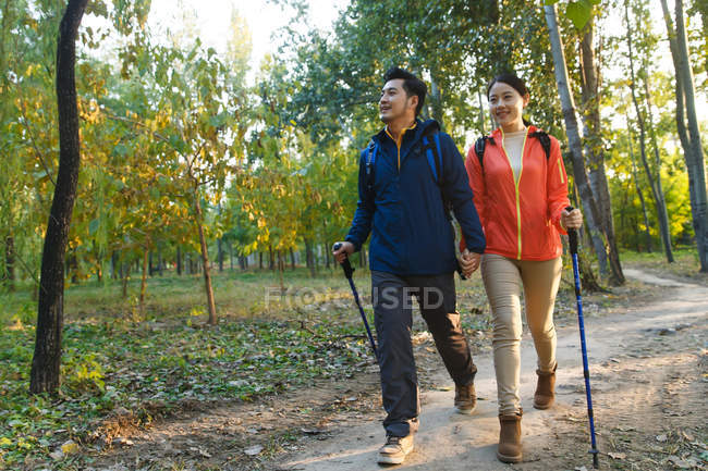 Smiling asian couple trekking in autumnal park — Stock Photo