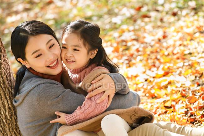 Aus der Vogelperspektive von glücklichen asiatischen Mutter und Tochter sitzen und umarmen im Herbst Park — Stockfoto