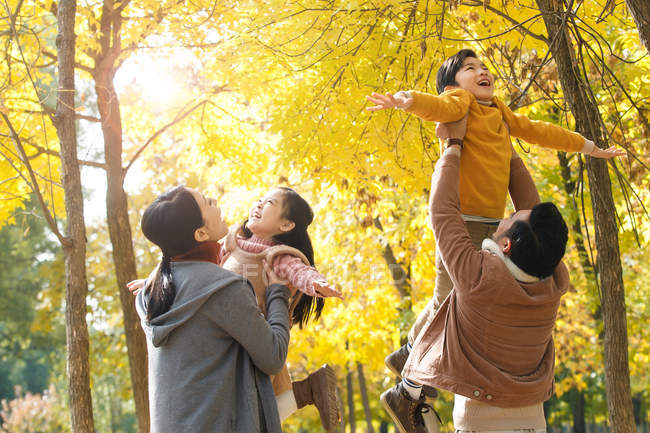 Happy young parents playing with adorable kids in autumn park — Stock Photo