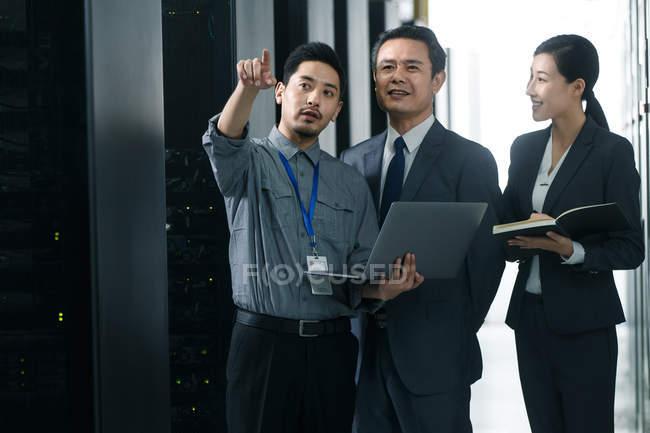 Персонал, работающий с ноутбуком и отводящий взгляд в комнате технического обслуживания — стоковое фото