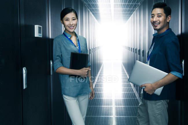 Professionelles, selbstbewusstes technisches Personal lächelt in die Kamera, während es im Wartungsraum arbeitet — Stockfoto
