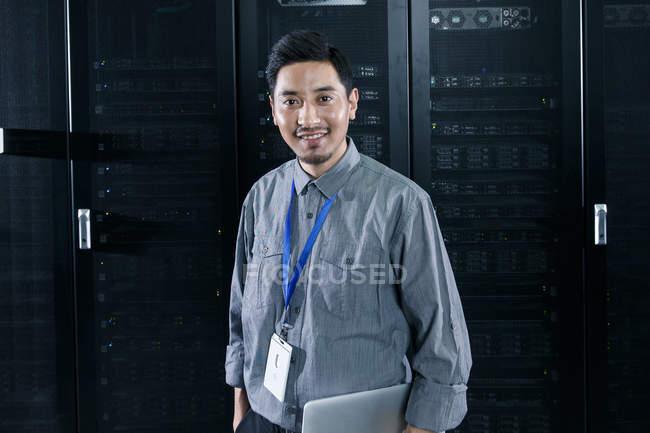 Рабочий держит ноутбук и улыбается камере в комнате технического обслуживания — стоковое фото