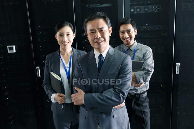 Technisches Personal lächelt während der Arbeit im Wartungsraum in die Kamera — Stockfoto