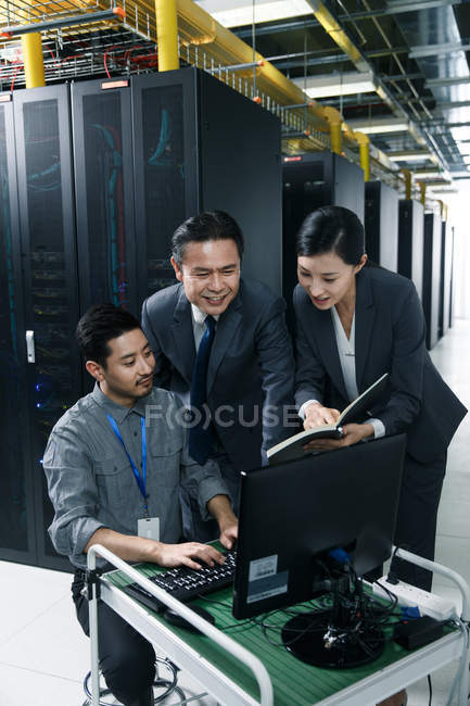 Technical personnel working with computer and notes in the maintenance room inspection — стокове фото