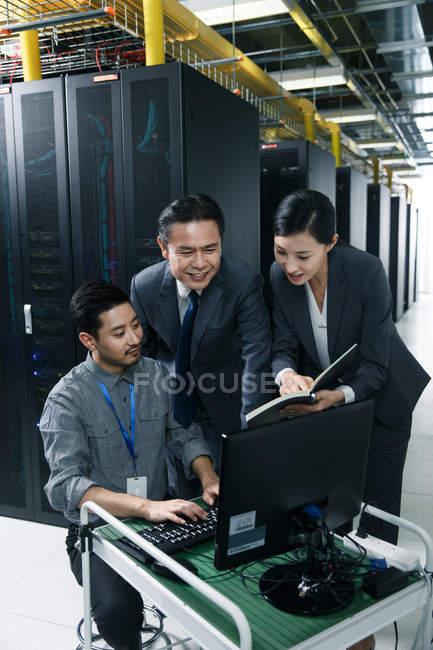 Pessoal técnico que trabalha com computador e notas na inspeção da sala de manutenção — Fotografia de Stock