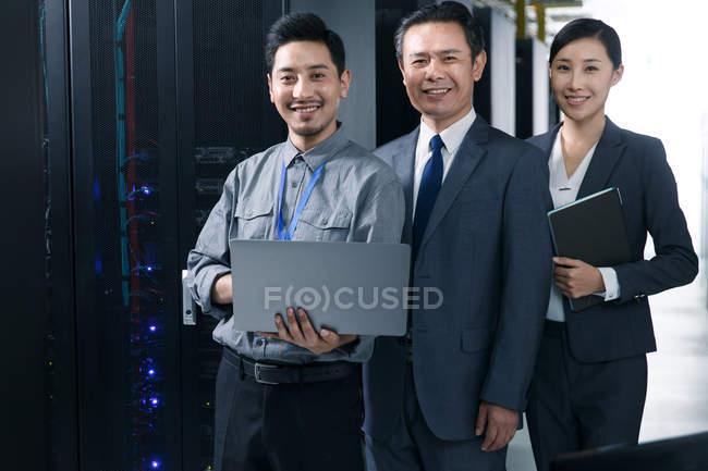 Personale tecnico sorridente alla macchina fotografica mentre lavora nell'ispezione della stanza di manutenzione — Foto stock