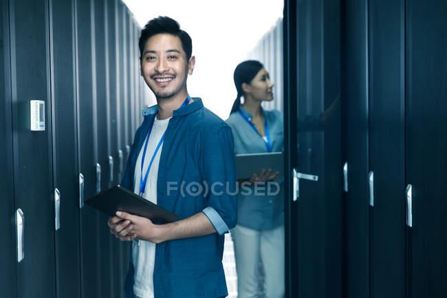 Рабочий-мужчина улыбается на камеру, а инженер-женщина работает в ремонтной мастерской — стоковое фото