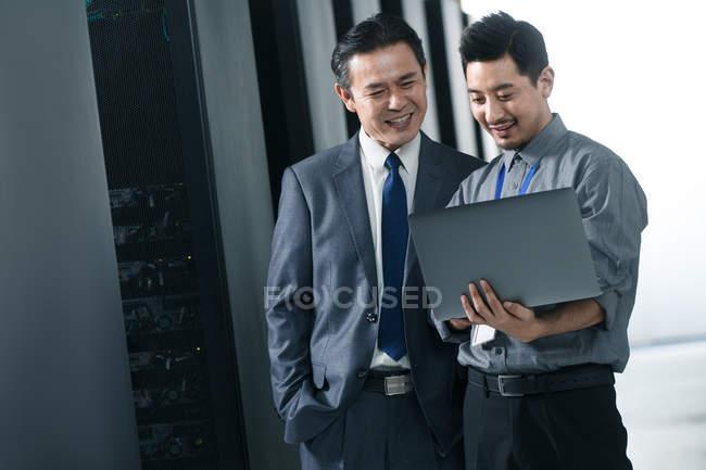 Personal técnico que trabaja con ordenador portátil en la inspección de la sala de mantenimiento. - foto de stock