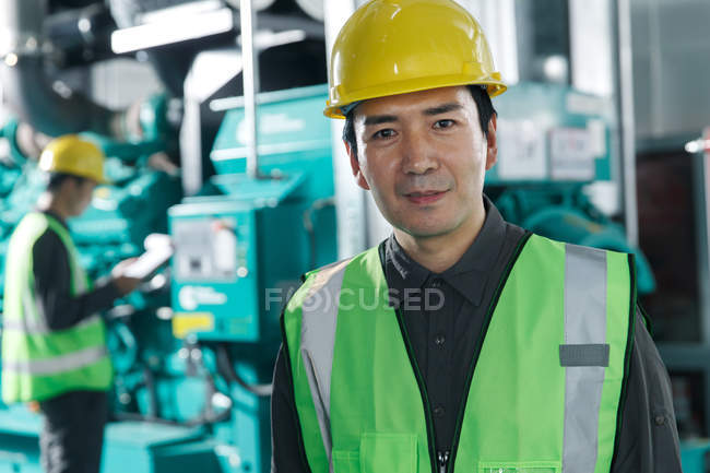 Professional male engineers in hard hats working in the factory — Stock Photo