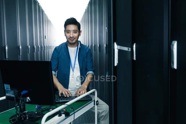 Personal técnico que trabaja con el ordenador en la inspección de la sala de mantenimiento. - foto de stock