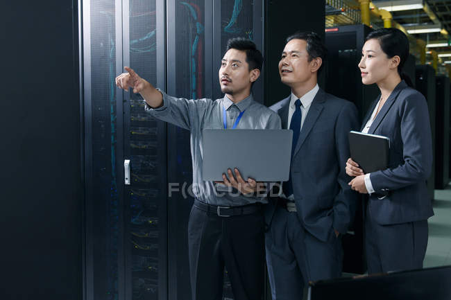 Technical personnel working with laptop and looking away in the maintenance room inspection — Foto stock