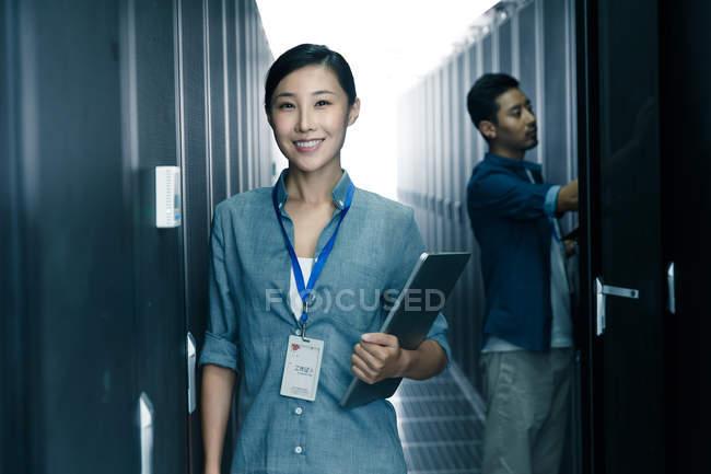 Работница улыбается на камеру, а инженер-мужчина работает в ремонтной мастерской — стоковое фото