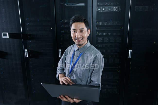 Персонал пользуется компьютером и улыбается перед камерой в комнате технического обслуживания — стоковое фото