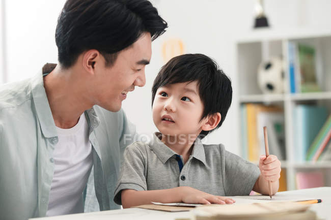 Smiling asian father teaching preschooler son at table at home — Stock Photo