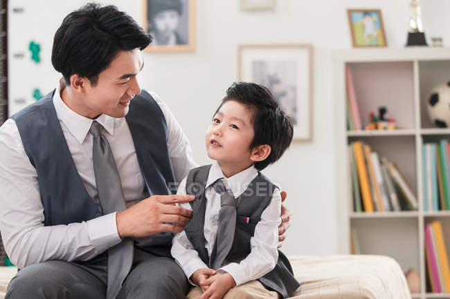 Smiling asian father and preschooler son in suits looking at each other at home — стоковое фото