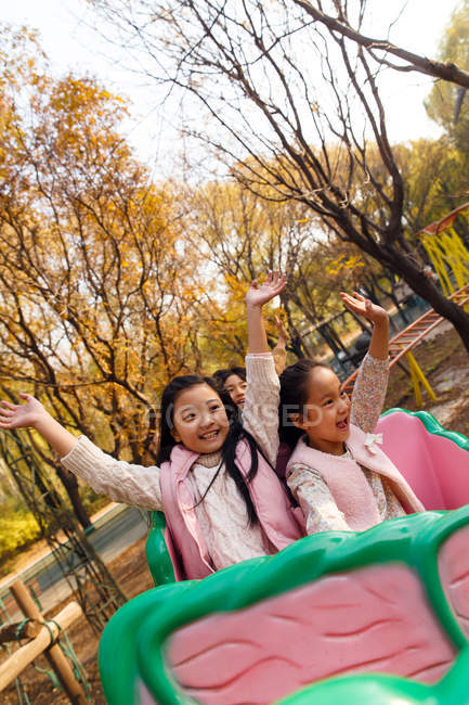 Happy boy and girls playing together on roller coaster in park — Stock Photo