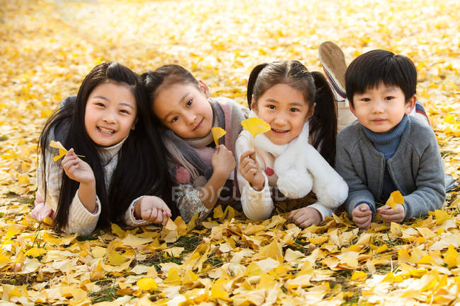 Happy boy and girls lying together on yellow leaves and smiling at camera in autumn park — стокове фото