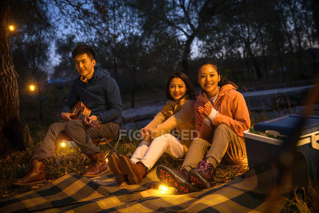 Three asian friends sitting on blanket with ukulele and looking at camera in autumnal evening forest — Stock Photo