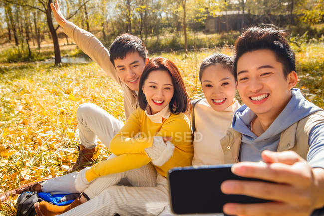 Four young smiling asian friends taking selfie with smartphone in autumnal forest — Stock Photo