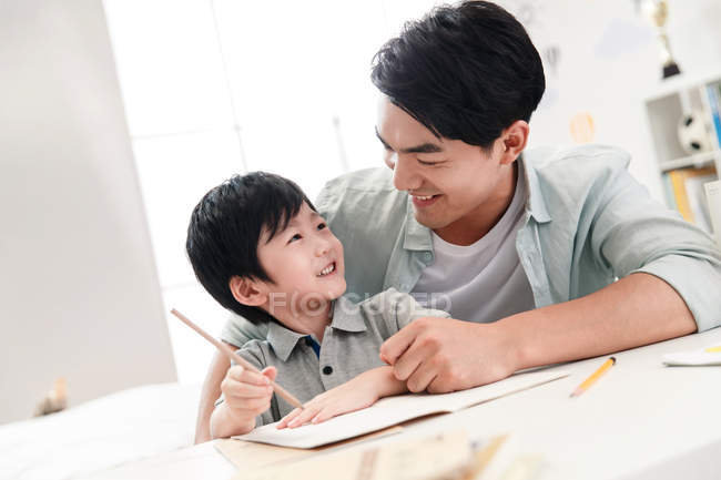 Smiling asian dad teaching preschooler kid at table at home — Stock Photo