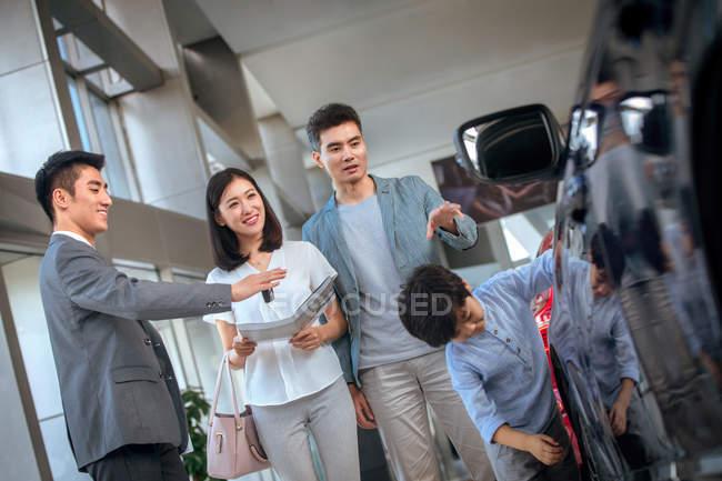 Азиатский продавец показывает автомобиль для счастливой семьи выбирая автомобиль в автосалоне — стоковое фото