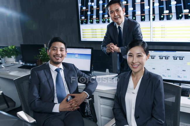 Профессиональные деловые люди улыбаются на камеру во время совместной работы в диспетчерской — стоковое фото