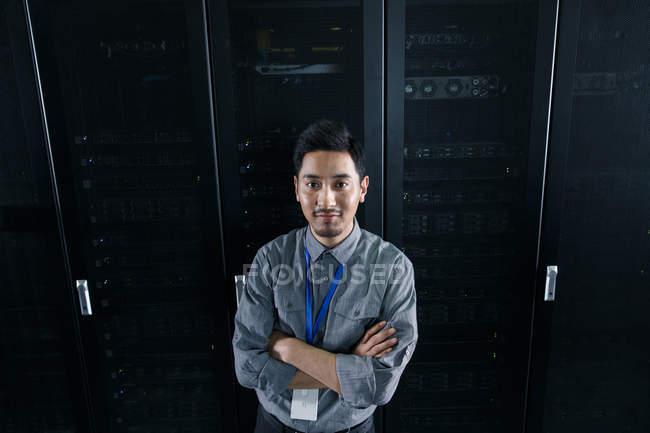 Alta angolazione vista di fiducioso lavoratore maschile in piedi con braccia incrociate e sorridente alla telecamera nel controllo della sala di manutenzione — Foto stock