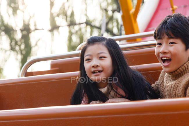 Щасливий хлопчик і дівчинка грають разом на дитячому майданчику. — стокове фото