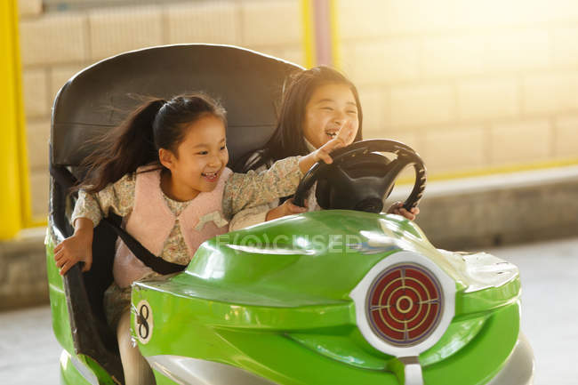 Adorable happy chinese girls riding car and playing together at playground — стокове фото