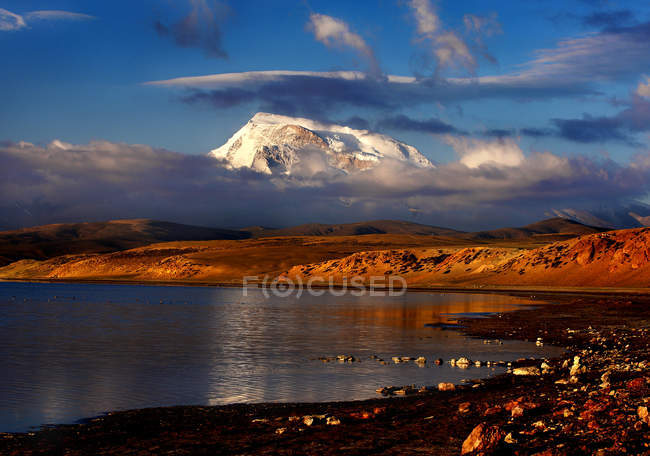 Amazing mountain landscape with snow-covered mountains and clouds in sky reflected in calm water of lake — стокове фото