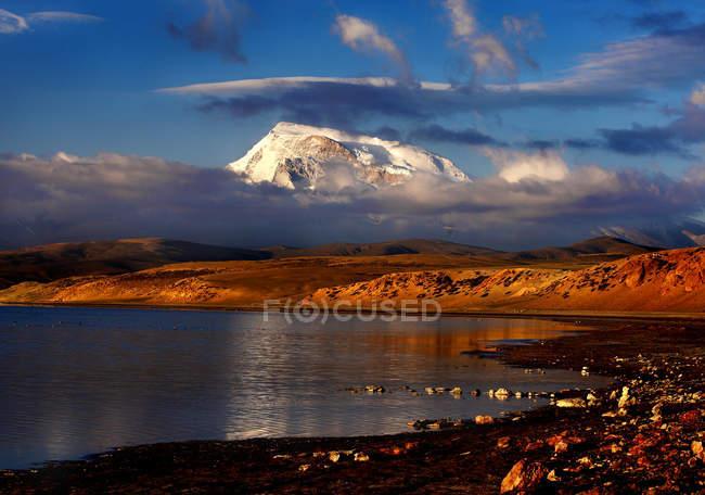 Asombroso paisaje montañoso con montañas cubiertas de nieve y nubes en el cielo reflejadas en aguas tranquilas del lago. - foto de stock